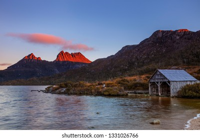 Beautiful evening, red alpine glow on Cradle Mountain.With old historic boat shed in foreground of Dove Lake.Cradle Mountain Lake St Clair National Park.Central Highlands of Tasmania,Australia.