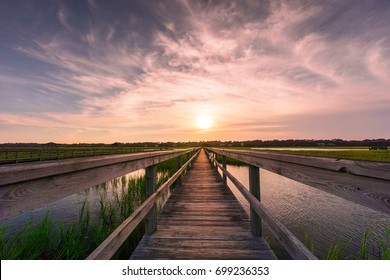 beautiful evening sky and sunset over a boardwalk on the marsh with marsh grass and high tide on a barrier island in South Carolina