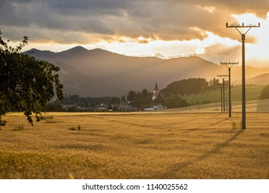 Beautiful evening sunset over field with grain. In the background electric power line, church and mountain. Country Slovakia, Europe.