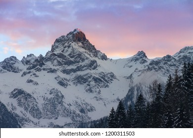 Beautiful evening sunset view of mountain tops with snow and vibrant clouds in the Brandnertal in the Alps in Vorarlberg, Austria, in winter