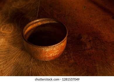 """A beautiful example of an Anagama fired ceramic bowl shot on a wood background. Used """"painting by light"""" for this exposure."""