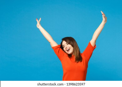 Beautiful excited brunette young woman wearing red orange dress raised hands up winner say Yes isolated over blue wall background studio portrait. People lifestyle fashion concept. Mock up copy space