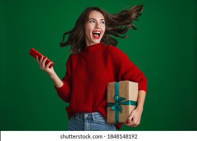 Beautiful excited girl screaming while posing with Christmas gift and cellphone isolated over green background - Shutterstock ID 1848148192