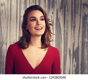 Beautiful excited laughing makeup woman happy in casual red shirt and short curly hair with empty copy space. Toned closeup portrait