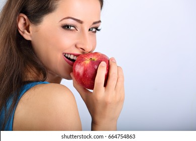 Beautiful excited makeup brunette woman biting the red tasty apple and looking happy with empty space blue background. Closeup portrait