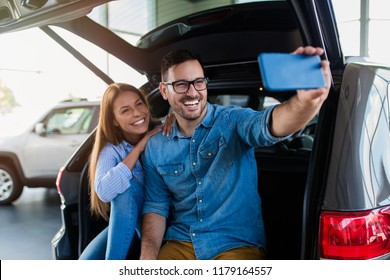 Beautiful excited young couple at car showroom taking selfie photo in their new car.