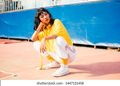 Beautiful exited cool woman with yellow t-shirthaving fun and sitting at amusement park at hot summer
