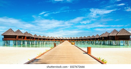 Beautiful exotic beach and wooden bridge to amazing exotic bungalows on turquoise water