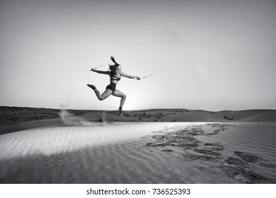 Beautiful exotic mixed race woman performs a jumping martial artist kata with escrima sticks in a desert at sunrise and sun flare in the background in black and white.