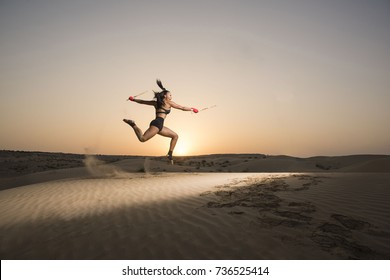 Beautiful exotic mixed race woman performs a jumping martial artist kata with escrima sticks in a desert at sunrise and sun flare in the background.