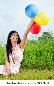 beautiful exotic teenage girl in green nature holding a bunch of colorful balloons