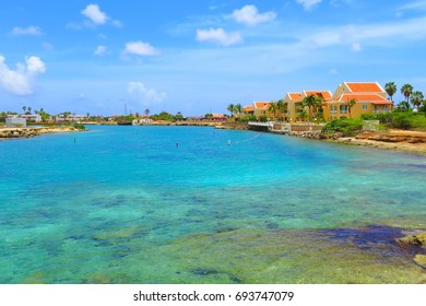 Beautiful exotic vacation lagoon with azure calm sea, palm trees and colored houses. Remote island with small resort by the tropical sea.