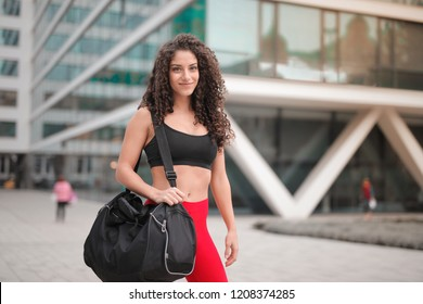 Beautiful exotic woman in a sporty outfit and with a duffle bag.
