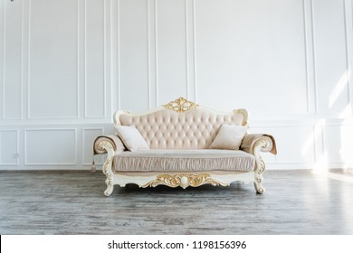 beautiful expensive beige sofa against a white wall in an empty room