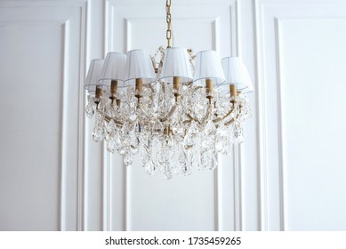 A beautiful expensive chandelier with many crystal crystals is hanging near a white wall.