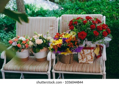 Beautiful and exquisite decoration of the wedding celebration in in the middle of a green garden. Two white armchairs with pillows on which there are congratulatory bouquets with flowers in boxes.