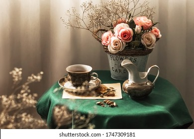 Beautiful exquisite vintage interior. A bouquet of delicate flowers, a cup of coffee and a milk jug on a table with a green tablecloth. Holiday decor. Copy space.
