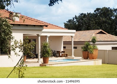 Beautiful exterior of the house with swimming pool on the porch and green grass lawn. Shot on summer day with blue skies