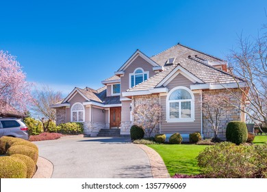 Beautiful exterior of newly built luxury home. Yard with green grass and walkway lead to ornately designed covered porch and front entrance.