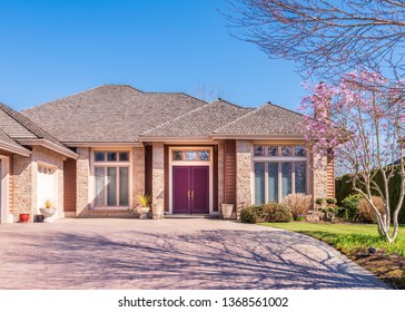Beautiful exterior of newly built luxury home. Yard with green grass and walkway lead to front entrance.