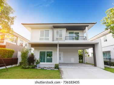 Beautiful exterior of newly home with green grass and blue sky during at sunrise.Front View of New Residential house for sale.Home For Sale,Rent,Housing and Real Estate concept.