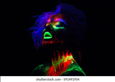 Beautiful extraterrestrial model woman with blue hair and green lips in neon light. It is portrait of beautiful model with fluorescent make-up, Art design of female posing in UV with colorful make up