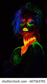 Beautiful extraterrestrial model woman with blue heair and green lips in neon light. It is portrait of beautiful model with fluorescent make-up, Art design of female posing in UV with colorful make up
