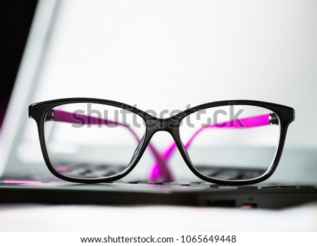 621a65af32 Beautiful eye glasses and laptop. Business optical background. Plastic lens  glasses and black frame