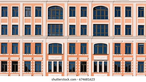 Beautiful facade of a building with yellow walls and white decor on the windows