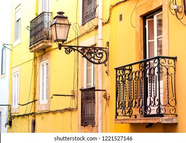 Beautiful facade in central Lisbon, Portugal. Ancient forged iron lamp and beautiful iron balcony against bright yellow wall.