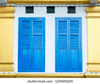 Beautiful facade detail with bright blue shutters on white and golden wall in Little India, Singapore
