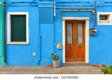 Beautiful facade with green shutters and  flowers and wooden door on blue wall. Colorful houses on Burano island near Venice, Italy