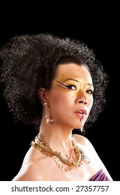 Beautiful face of an Asian woman with black curly fro hair, gold with purple makeup, bare shoulders and luxury necklace, isolated