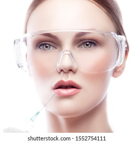 Beautiful face of beatician with syringe needle near lips wearing medical protective glasses