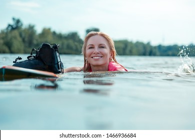 Beautiful face. Closeup portrait of a beautiful smiling Caucasian woman with loose blond hair floating in the water next to her wakeboard