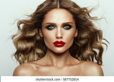 Beautiful face of a fashion model with blue eyes.Curly hair. Red lips. Studio portrait.