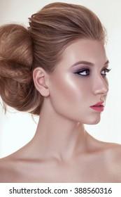 Beautiful face of a fashion model. Pink glitter. Curly hair. Pink lips. Studio portrait. Warm skin.