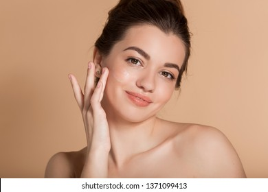Beautiful face portrait of young woman is applying face cream on a cheek. Skin care and health concept.