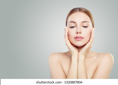 Beautiful face. Pretty woman holding her face in her hands. Facial treatment, face lifting, anti aging and skin care concept.