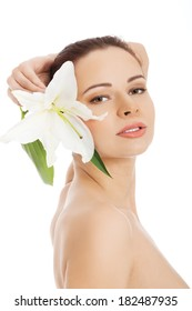 Beautiful face of spa woman with healthy clean skin and lily flowers