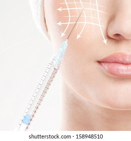 Beautiful face and the syringe (plastic surgery and cosmetic injection concept)