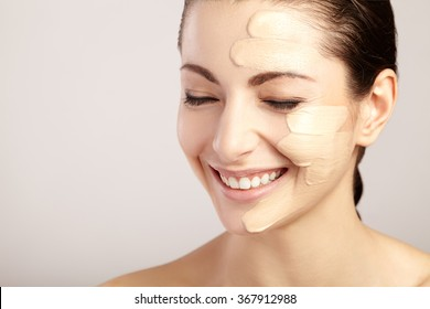Beautiful face of woman with cosmetic foundation on skin