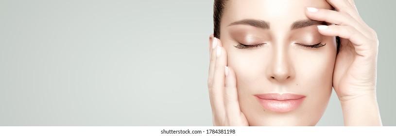 Schöne Gesichtsfrau mit frischer, sauberer Haut. Gesunde Hautfrauen, die sich anmutig die Hände im Gesicht halten. Kosmetologie Schönheitspalast und Hautpflege. Nahaufnahme eines Porträts auf einem Panoramabanner mit Kopienraum