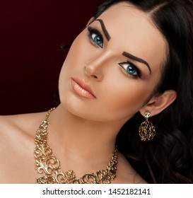 Beautiful face woman, has big blue eyes, long eyelashes, brunette hair, sexy lips, decorations gold bijouterie jewelry. Eastern arabic  female portrait. Luxury fashion make up. Close up.