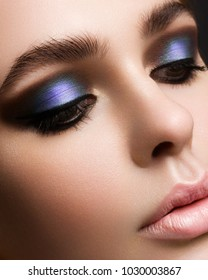 Beautiful face of the woman with ideal skin. Evening bright cosmetics. Eyelashes are long. Black and green colors of cosmetics. Equal tone of skin.