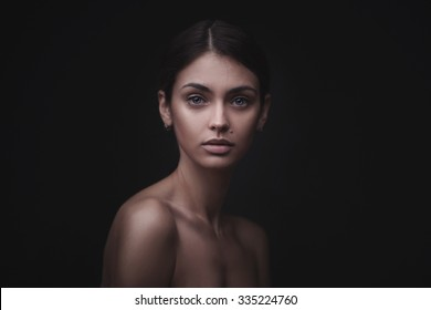Beautiful face of young adult woman with clean fresh skin isolated on black background