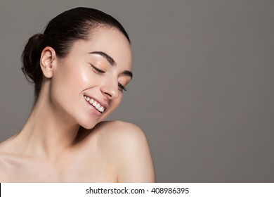 Beautiful face of young adult woman with clean fresh skin and bare shoulders on grey background.