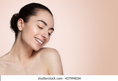 Beautiful face of young adult woman with clean fresh skin and bare shoulders on brown background.