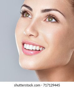 Beautiful face of young adult woman with clean fresh skin. Amazing smile, perfect teeth.