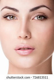 Beautiful face of young adult woman with clean fresh skin. Long eyelashes.